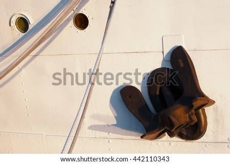 Closeup view of ship anchor and portholes. - stock photo