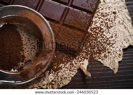Closeup view of silver sieve with cocoa powder and chocolate bar, retro style - stock photo
