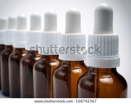 Closeup view of sorted bottles with droppers. - stock photo
