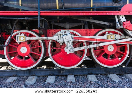 Closeup view of steam locomotive wheels, drives, rods, links and other mechanical details. White, black and red colors - stock photo