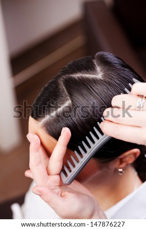 Closeup view of the hand and comb of a hairstylist combing a new hairstyle on a customer with a zig zag parting - stock photo