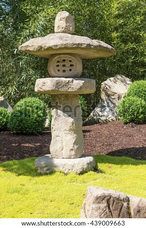 Closeup view of the Japanese stone lamp in the Japanese garden. Green plants and trees are in the background. - stock photo