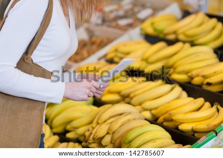 Closeup view of the torso and hands of a female shopper buying ripe yellow bananas holding her shopping list in her hands - stock photo