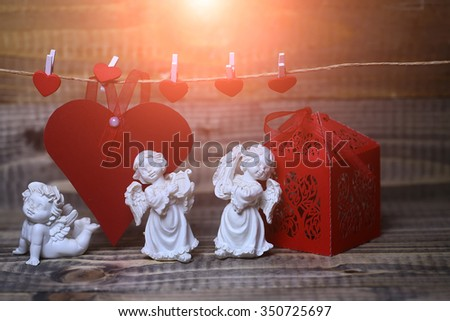 Closeup view of three beautiful cupid angels decorative figurine near red paper greeting valentine box and card on hanging ribbon on clothes-peg with no people on wooden background, horizontal picture - stock photo