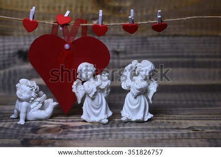 Closeup view of three beautiful cupid angels decorative figurine near red paper greeting valentine card on hanging ribbon on clothes-peg with no people on wooden background, horizontal picture - stock photo