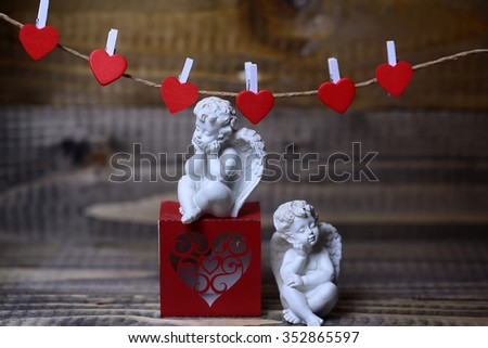Closeup view of two beautiful cupid angels decorative figurine near red paper greeting valentine box near clothes-peg in shape of heart with no people on wooden background, horizontal picture - stock photo