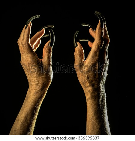Closeup view of two female old scary mystic hands with long black nails on fingers of witch zomby demon or devil on halloween holiday character in studio indoor on dark background, square picture - stock photo