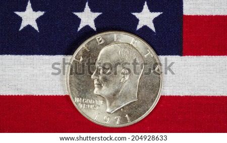 Closeup view of United States Silver Dollar Coins, President Eisenhower, placed on American Flag  - stock photo
