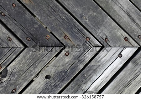 Closeup view of v shape timber planks joint with nails and bolts. - stock photo