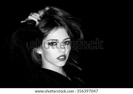 Closeup view portrait of one attractive enigmatic sensual pensive young woman with long hair and raised hands in black cloth in evening outdoor black and white copy space, horizontal picture - stock photo