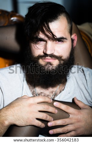 Closeup view portrait of one handsome serious young adult man with long black lush beautiful beard and moustache looking forward holding sexe female legs in stockings indoor, vertical picture - stock photo