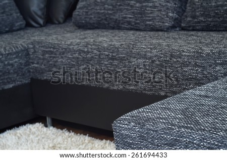 Closeup view to modern black and white cloth sofa with black leather, pillow and shaggy carpet - stock photo