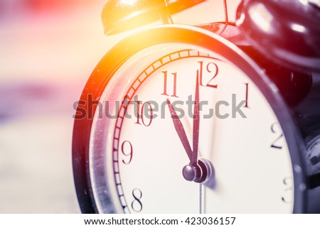 closeup vintage clock selective focus at number 11 o'clock with sun light vintage color tone for postcard. - stock photo