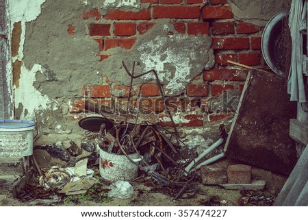 Closeup, vintage. The collapse of the plaster with brick wall of an old rural house. Old broken utensils, junk, trash.  - stock photo
