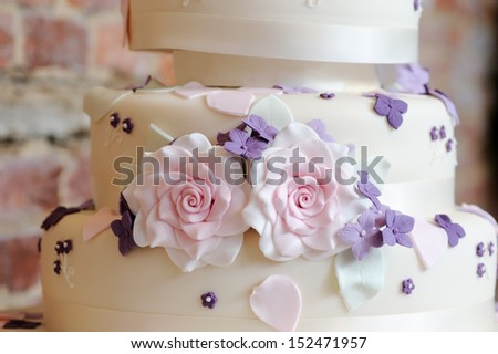 Closeup wedding cake decoration of pink and purple flowers at reception - stock photo