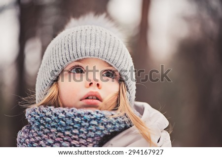closeup winter portrait of adorable baby girl looking up in knitted hat and scarf - stock photo