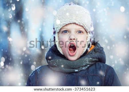 Closeup winter portrait of young shouting boy in hat, scarf and jacket at falling snow background. - stock photo