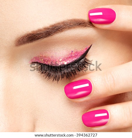 Closeup woman face with pink nails near eyes. Fingernails with pink manicure - stock photo