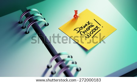 Closeup Yellow Sticky Note paste it in a notebook setting an appointment. The words Drink more water written on a white notebook to remind you an important appointment. - stock photo