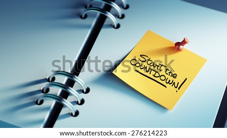 Closeup Yellow Sticky Note paste it in a notebook setting an appointment. The words Start Countdown written on a white notebook to remind you an important appointment. - stock photo