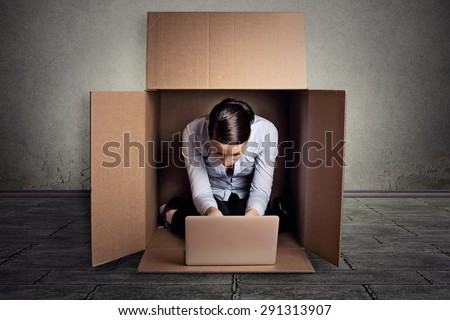 Closeup young introvert businesswoman hiding sitting in the carton box working on laptop computer  - stock photo