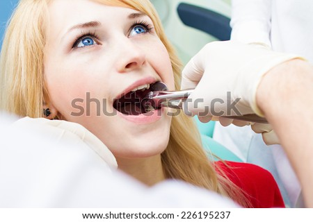 Closeup young woman at dentist clinic office. Male doctor and assistant performing extraction procedure with forceps removing patient tooth. Healthcare dentistry medicine concept  - stock photo