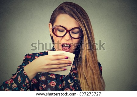 Closeup young woman sneezing isolated on gray wall background. Studio shot.  - stock photo