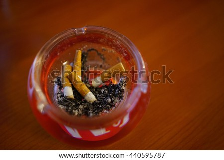 Closup wiew of full ashtray on a wooden table. - stock photo