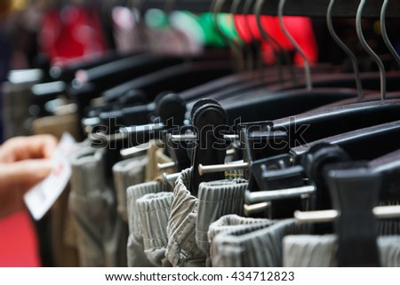 Cloth Hangers with trousers in Clothing store - stock photo