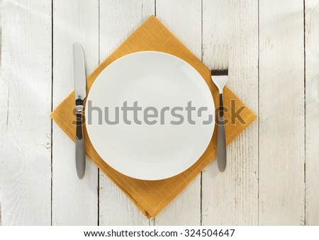 cloth napkin and plate on wooden background - stock photo