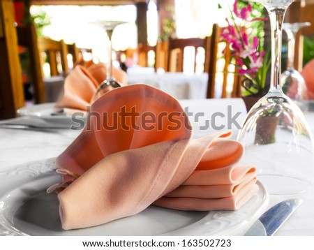 cloth napkin on a white plate on a restaurant table - stock photo
