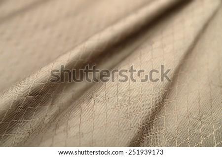 cloth wavy folds of grunge silk texture satin velvet material in brown gold color, elegant wallpaper design - stock photo