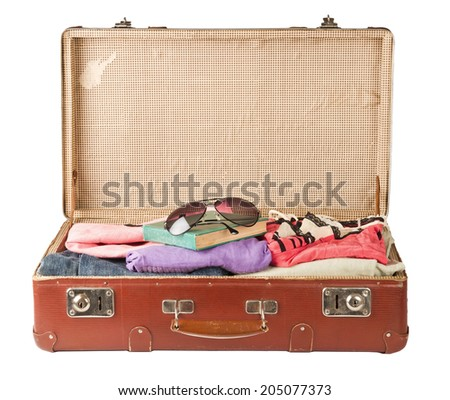 Clothes and book, glasses on old suitcase isolated on white - stock photo