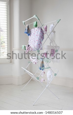 Clothes drying on laundry airer in domestic room - stock photo