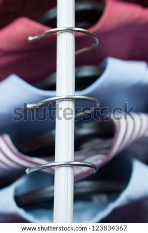 Clothes hangers with shirts in the fashion store - stock photo