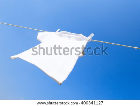 clothes hanging on a clothesline in front of blue sky - stock photo