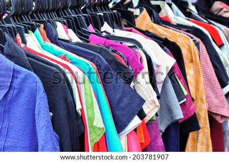 Clothes hanging on a rack in a flea market - stock photo