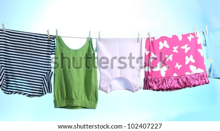 Clothes hanging on a rope on blue - stock photo