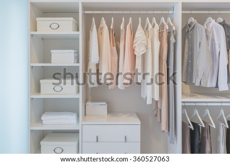 clothes hanging on rail in white wardrobe with boxes - stock photo