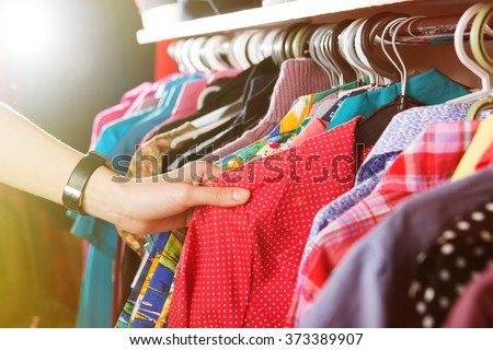 Clothes hanging on the rack in the fashion store - stock photo