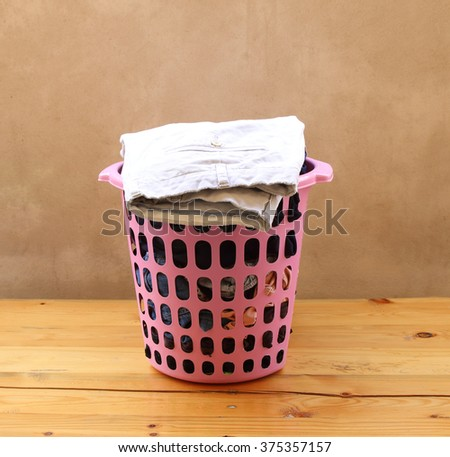 Clothes in a laundry basket on table - stock photo
