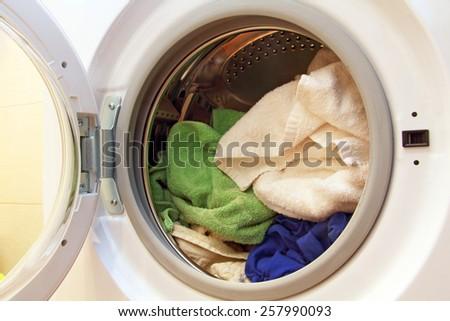 Clothes inside of washing machine taken closeup. - stock photo
