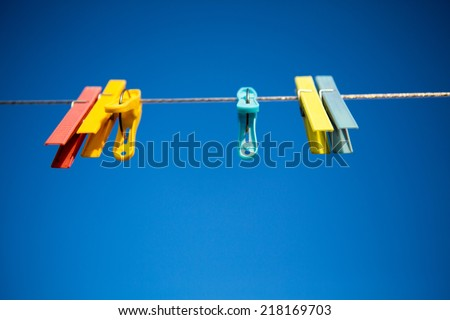 Clothes line with colored clothespins against a blue sky background - stock photo