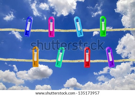 Clothes line with pegs against the blue sky - stock photo