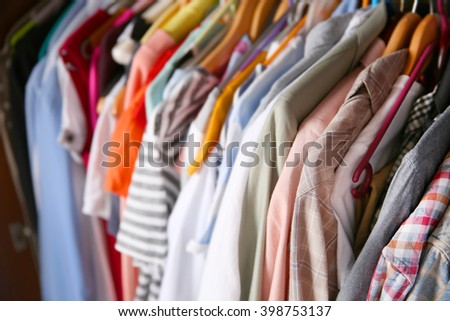 Clothes neatly hanging in the closet, close up - stock photo