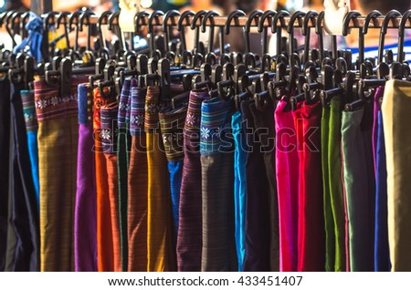clothes on a rack on a flea market, A collection of Thai silk cloths and Multicolored striped - stock photo