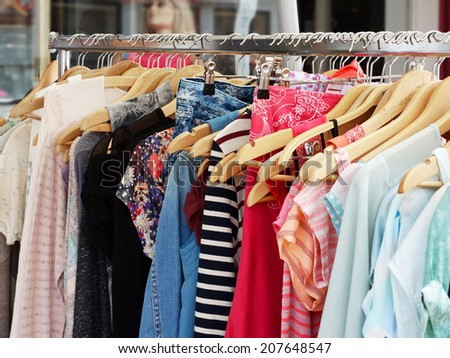 clothes rack with a selection of ladies fashion - stock photo