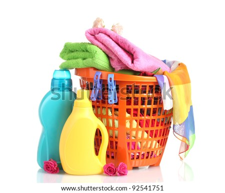 Clothes with detergent in orange plastic basket isolated on white - stock photo