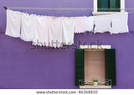 Clothesline at a purple house in Burano, one of the islands around Venice in Italy - stock photo