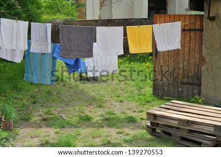 Clothesline with colorful towels in a garden in summertime - stock photo